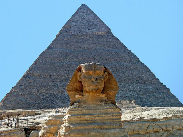 Voor een piramide rust een metershoge sfinx, een leeuw met mensenhoofd.