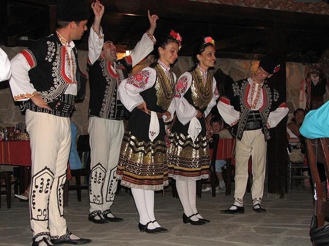 Dansers in traditionele Bulgaarse kleding buigen voor hun publiek.