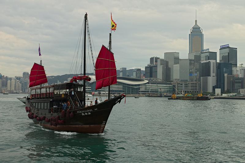 Een jonk (Chinese zeilboot) met op de achtergrond de wolkenkrabbers van Hong Kong