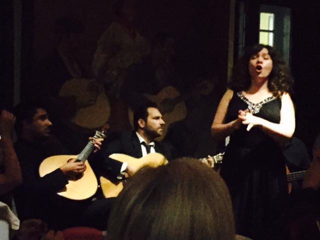 Een fadozangeres begeleid met Portugese en klassieke gitaar. Op de achtergrond een schilderij met precies hetzelfde tafereel.