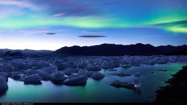 Een gletsjer baadt in het groene noorderlicht.