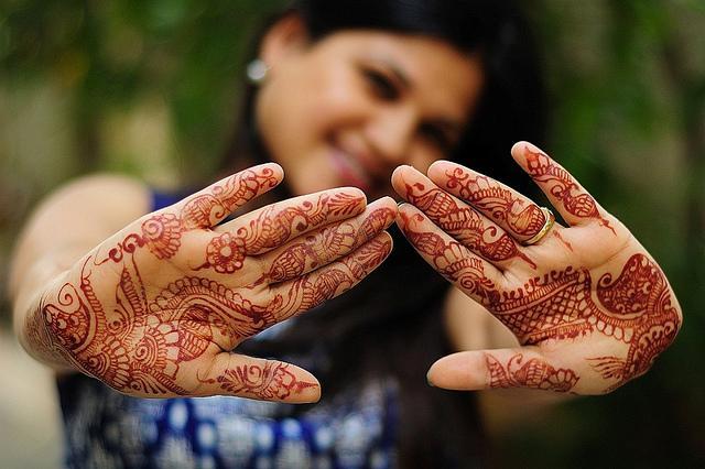 Een jonge vrouw pronkt met haar fraai beschilderde handen.