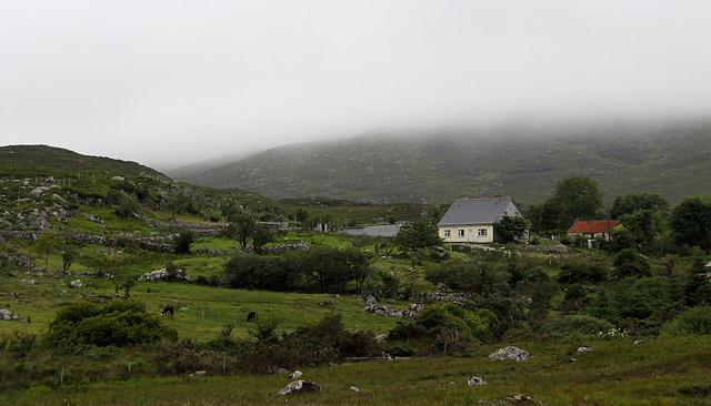Onder een mistig grijze hemel zijn een paar huisjes tussen de groene heuvels gestrooid.