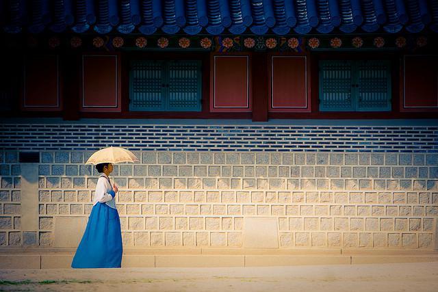 Een poëtische foto uit Seoul, Korea: een vrouw met blauwe jurk en witte parasol wandelt voorbij.