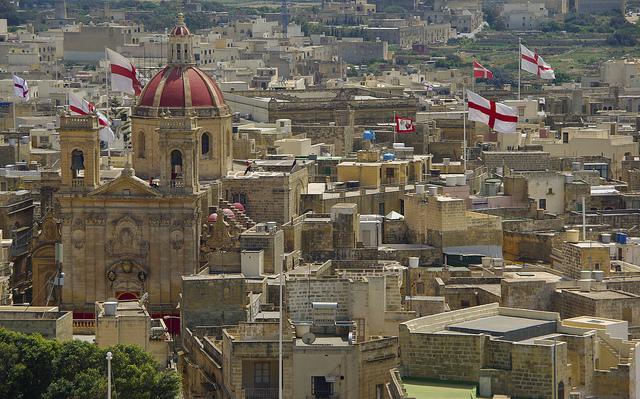 Zicht op de stad, met veel Maltese vlaggen en de rode dakkoepel van de kathedraal van Gozo.