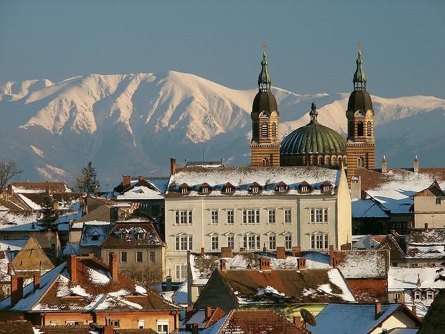 Twee torens en het koepeldak van de orthodoxe kathedraal, tegen een achtergrond van besneeuwde bergtoppen.