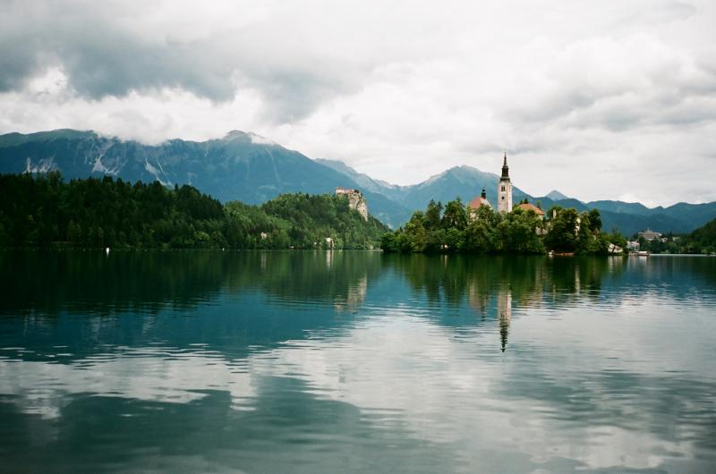 Bergen weerspiegelen in het meer. Midden in het water prijkt een kerk.