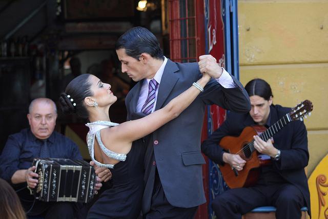 Begeleid met gitaar en bandoneon dansen een man een vrouw de tango in Buenos Aires.