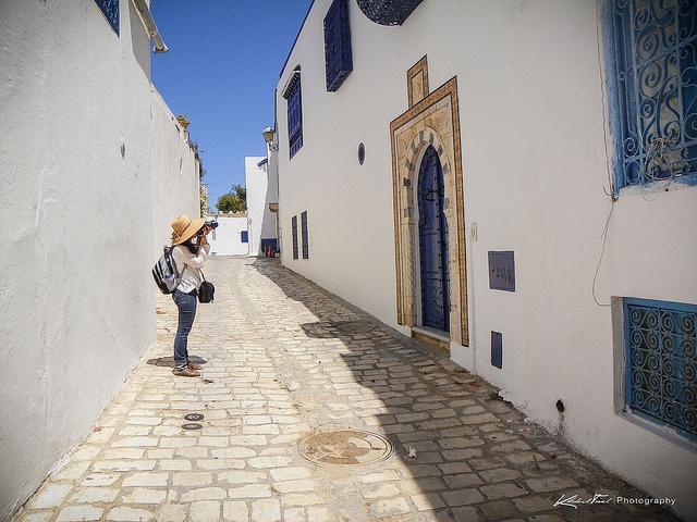 Een toerist fotografeert de helblauwe deur van een wit huis in een zonovergoten straatje in Tunis.