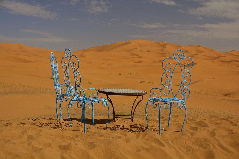 Twee sierlijke azuurblauwe stoelen en een rond tafeltje staan klaar voor de thee in een woestijnlandschap.