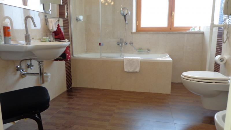 Badkamer, met ligbad, wastafel en toilet.