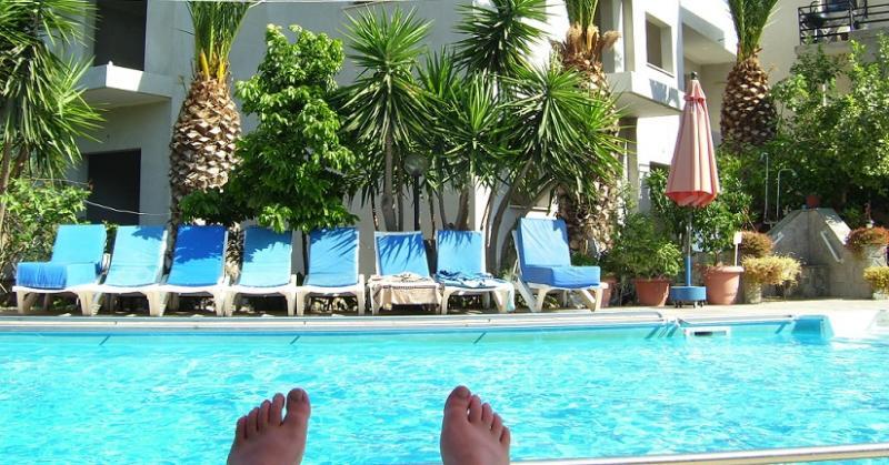 Buitenzwembad met zonneterras, gefotografeerd vanop een ligbed.