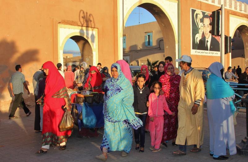 Vrouwen, mannen en kinderen, allemaal in felgekleurd kleding, staan bij een ronde okergele stadspoort.