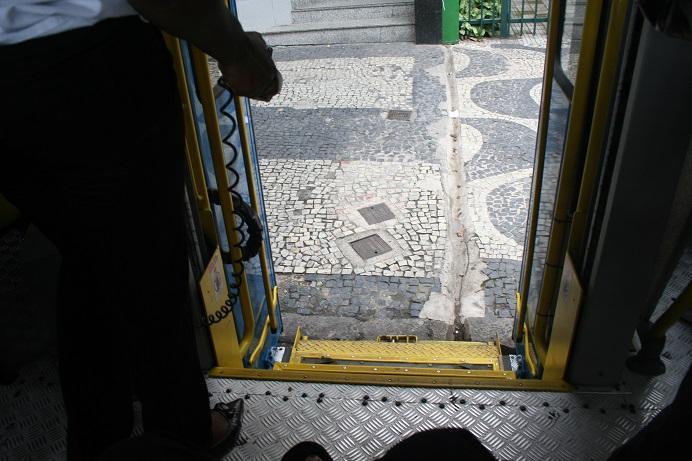 Plateaulift in stadsbus, ingeklapt aan een voetpad.