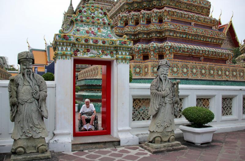 Jozef lacht ons toe door een ingang van de tempel, met een hoge drempel.