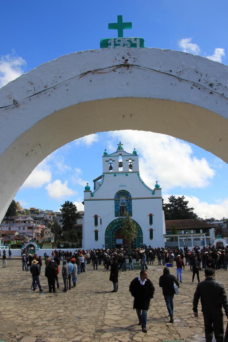 Een marktplein met wit kerkgebouw. Op een toegangspoort staat het jaartal 1954 vermeld.