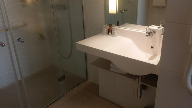 Wastafel naast de douche, met extra brede rand voor benodigdheden.
