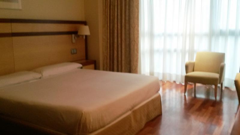 Slaapkamer met tweepersoonsbed en stoel aan het grote raam.