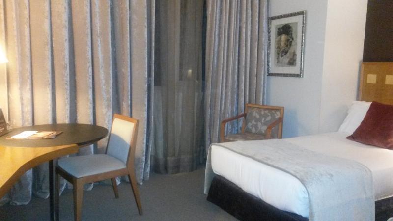 De rest van de slaapkamer: een schrijfmeubel en een groot raam (met de gordijnen dicht, want het was al donker buiten).
