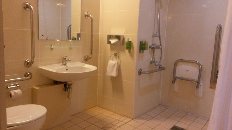 Aangepaste badkamer, met drempelloze douche en douchezit.