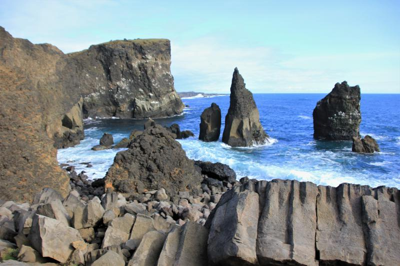 Grillige klippen in azuurblauwe zee.