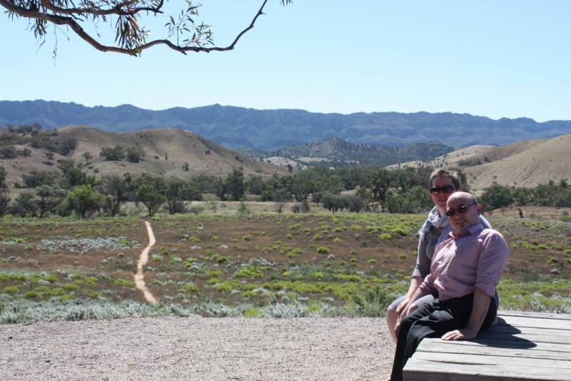 Op een bankje met een wijds landschap op de achtergrond.