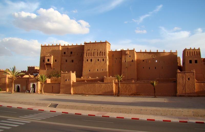 De kasbah is een groot zandstenen gebouw met veel kleine raampjes.