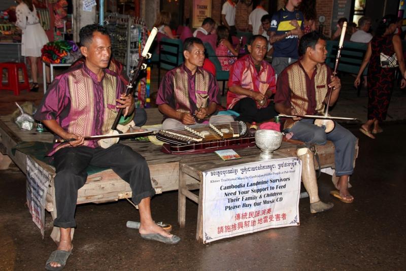 Een groepje mensen met een handicap bespelen traditionele muziekinstrumenten.