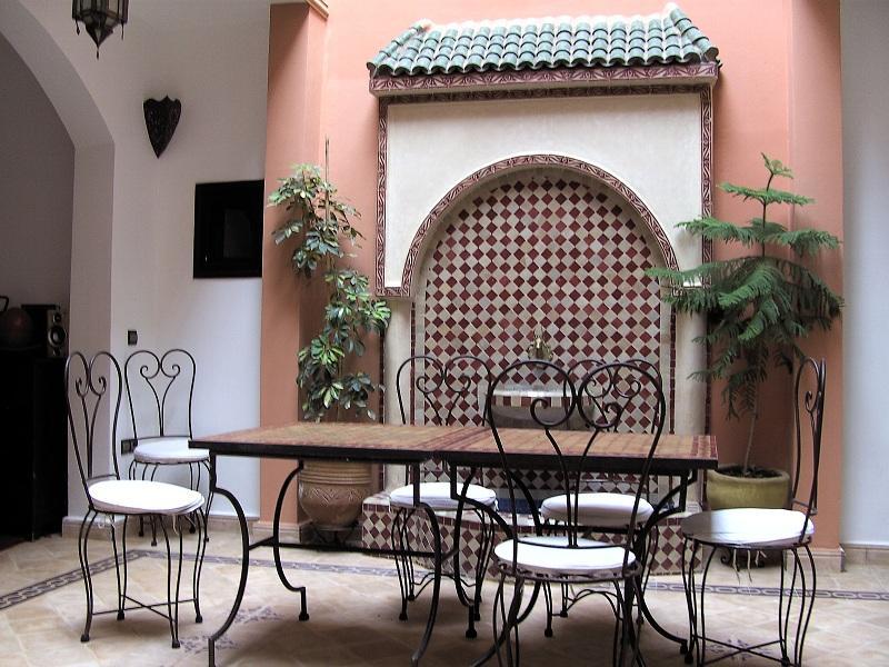 """Tafel en stoelen in een typisch-Marokkaanse living, met een betegelde """"schouw"""", witte muren en boogjes."""