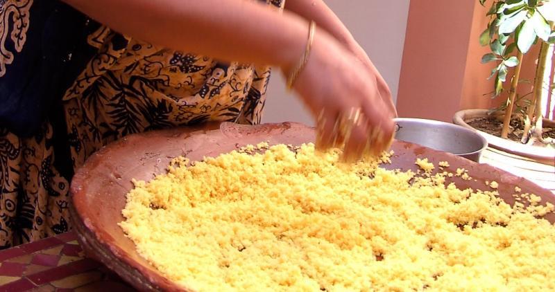De kokkin roert met de hand in een grote pan met goudgele couscous.