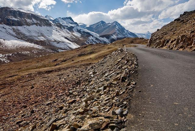 Een goed verharde weg tussen de losse stenen leidt naar besneeuwde bergtoppen.