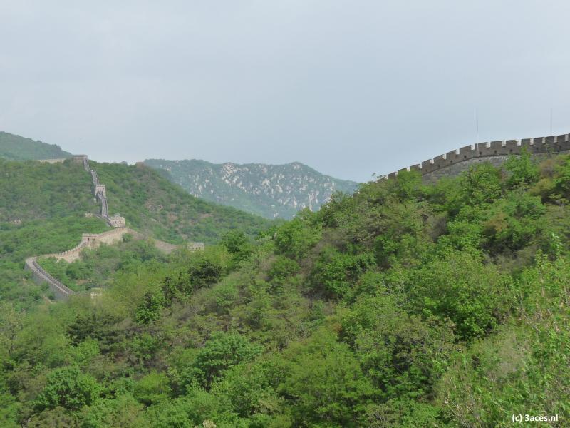 De Chinese Muur kronkelt tot ver voorbij de horizon door de groene heuvels.