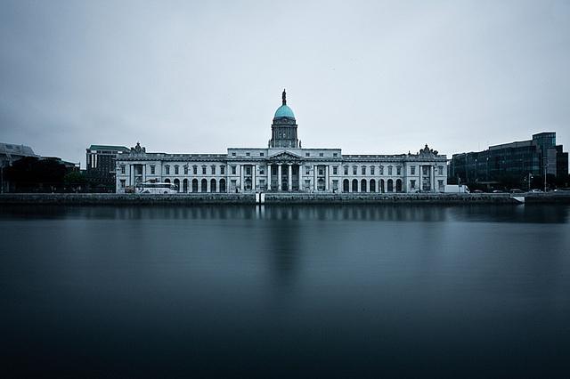 Groot gebouw in neo-klassieke stijl, gezien vanaf de overkant van de rivier.