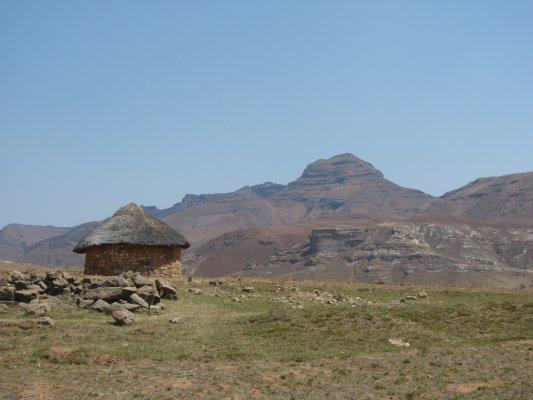 Een traditionele hut met  bergen op de achtergrond.