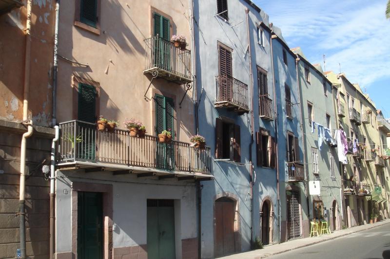 Huizenrij in pastelkleuren, een paar stoelen langs de straat, daarboven een waslijn.