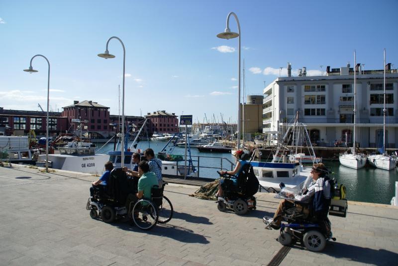Zes vrienden, allen rolstoelgebruikers, op wandel langs de jachthaven van Genua.