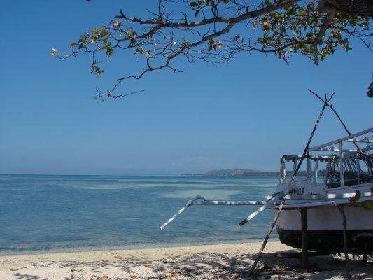 Een Balinese boot wacht op het strand om weer uit te varen.