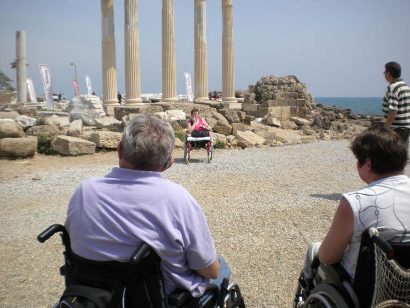Enkele rolstoelers bekijken antieke zuilen.