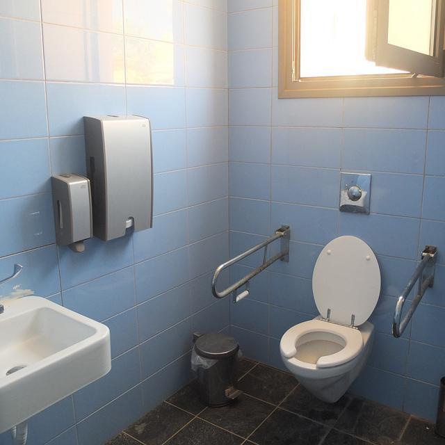 Toegankelijk toilet met twee handgrepen en onderrijdbare wastafel.