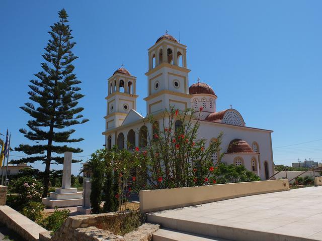 Een witte kerk met drie torens tegen een staalblauwe zomerlucht.