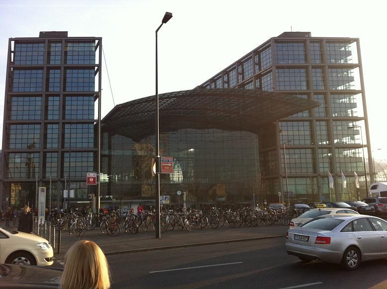 De gevel van het station bestaat grotendeels uit glas. Veel fietsen aan de voorkant: dit is fietstad Berlijn.