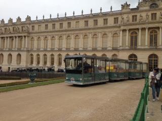 Het treintje van het domein van Versailles met het kasteel op de achtergrond.