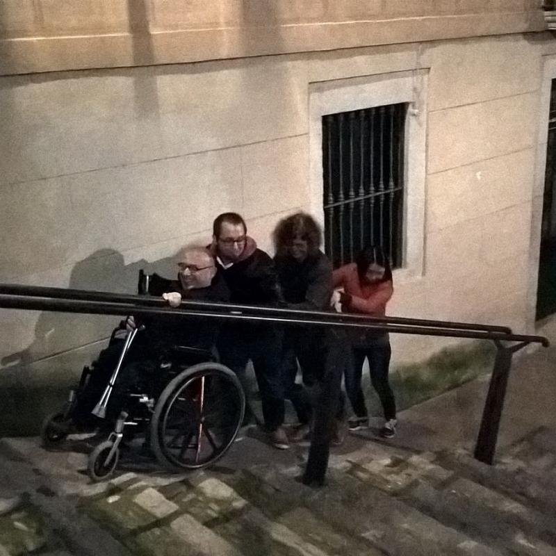 Drie mensen helpen Pieter (in rolstoel) bij het nemen van een steile helling.
