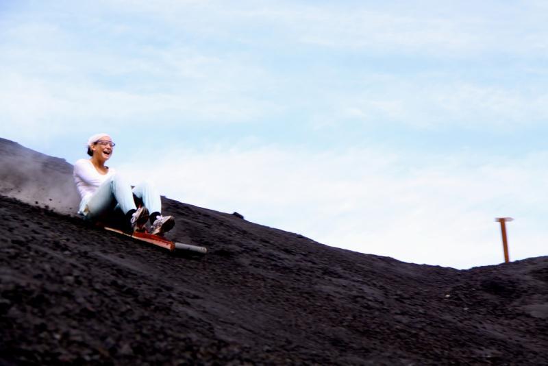Mei Lan daalt op een sandboard de vulkaan af.