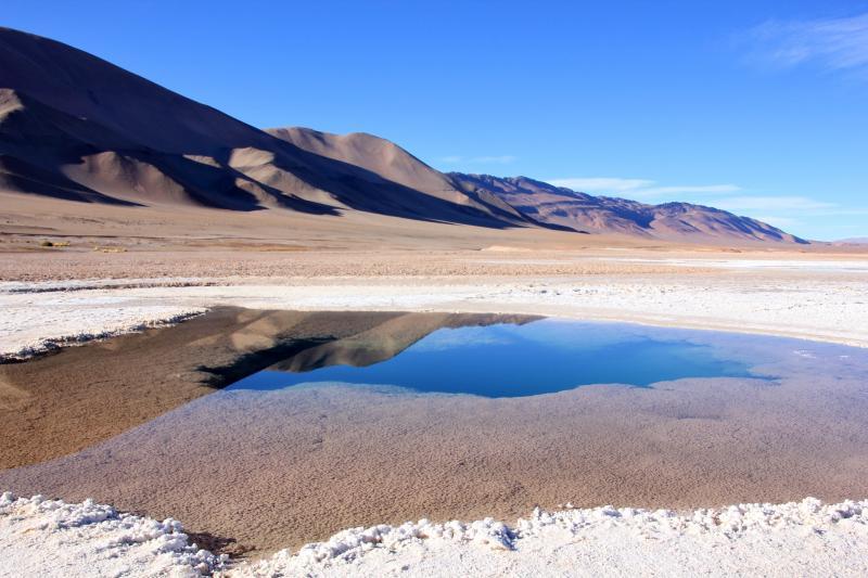 De blauwe lucht en de heuvels spiegelen in het heldere water.
