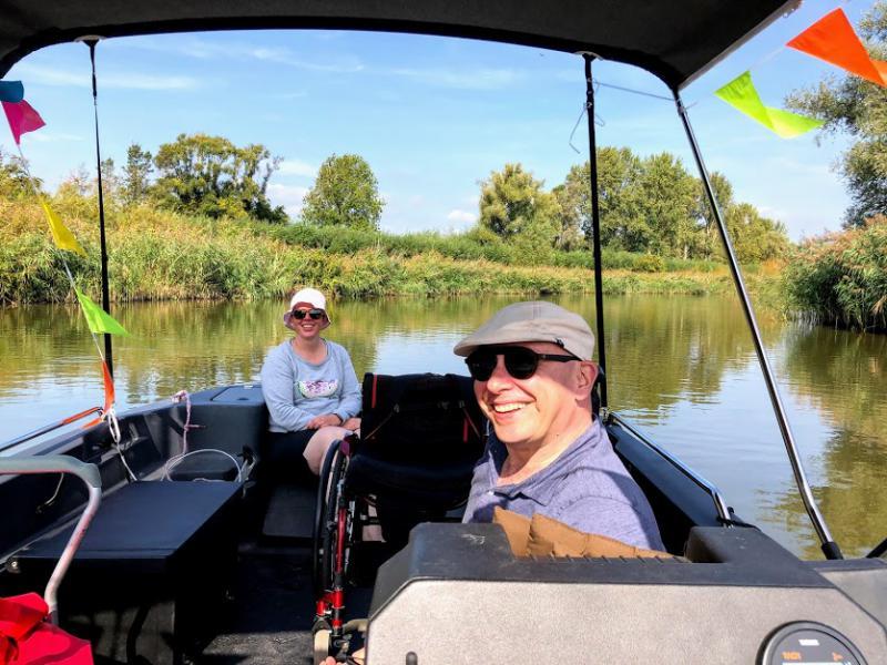 Pieter aan boord, met het natuurgebied op de achtergrond.