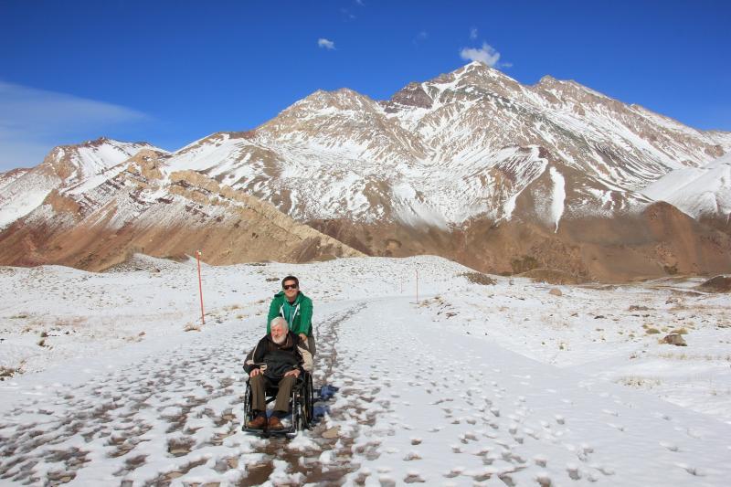 Gids Mariano duwt de rolstoel van Jozef door de sneeuw. Op de achtergrond, besneeuwde bergtoppen.