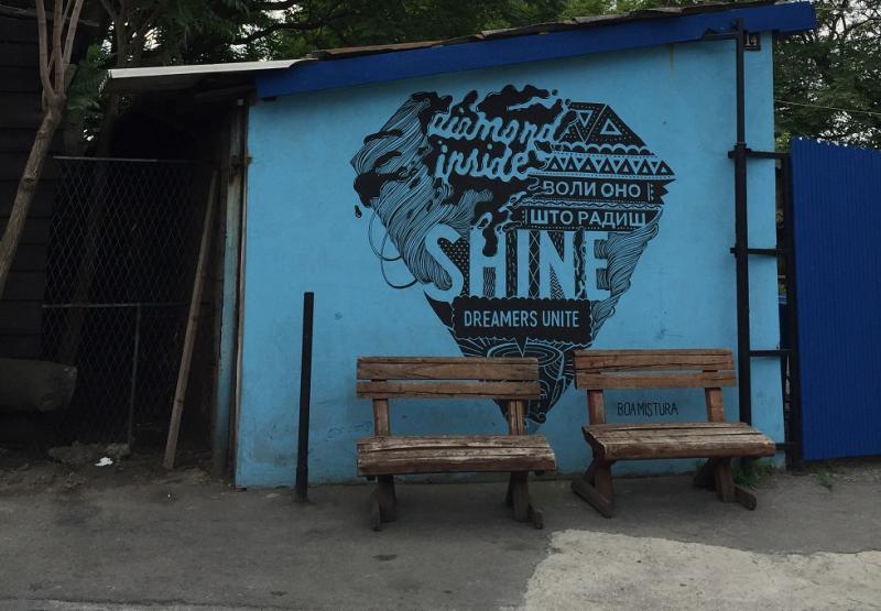 """Muurschildering in de vorm van een diamant, met daarin de woorden """"Shine"""" en """"Diamond inside - dreamers unite""""."""