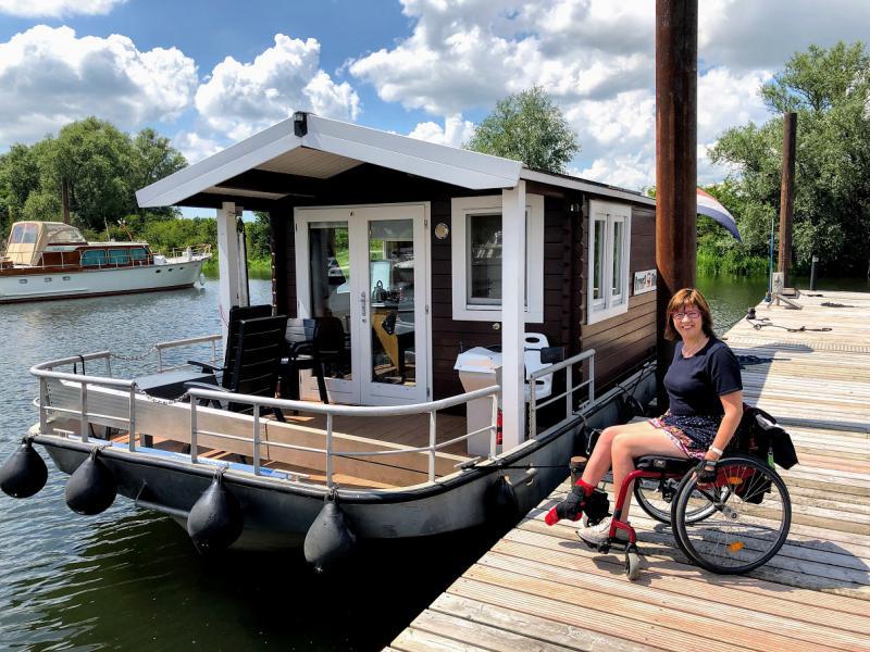 Vanja poseert met haar rolstoel naast de boot.