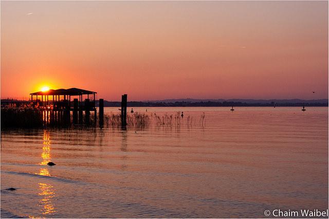 De zon gaat onder boven het Gardameer.